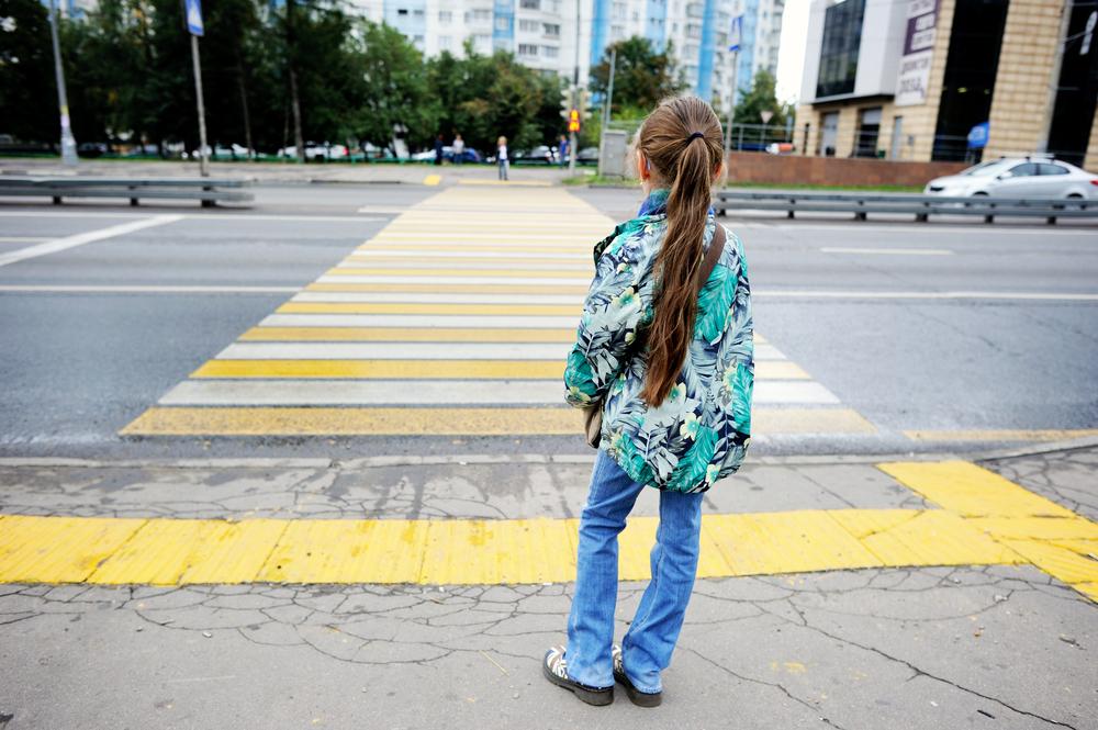 copil care trece strada